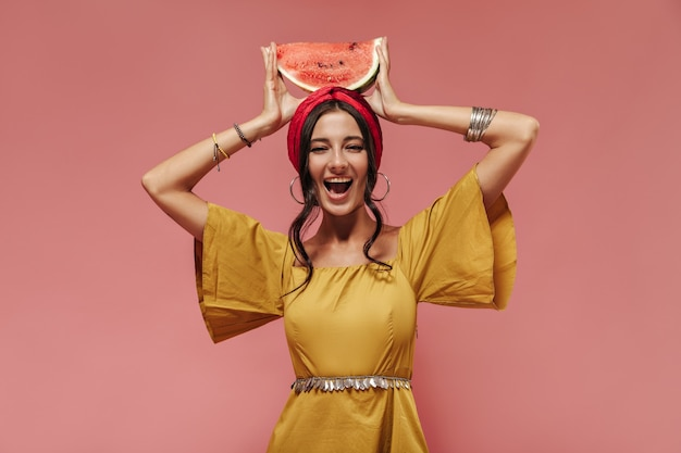Positive süße frau mit lockigem haar in stilvollen accessoires und hellem, modernem sommerkleid, die lacht und wassermelone auf der hand hält