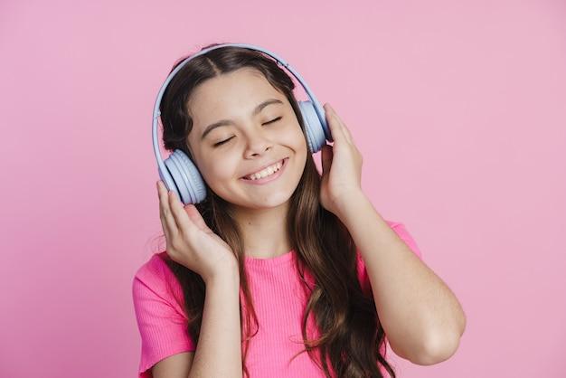 Positive teenager-mädchen in kopfhörern hört musik. das mädchen genießt die musik, schloss die augen vor einem rosa hintergrund