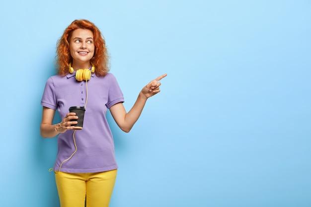 Positive teenager-mädchen mit roten kurzen haaren, zeigt auf freien platz, hält pappbecher kaffee