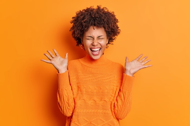 Positive überglückliche junge frau hebt handflächen fühlt sich sehr froh, drückt freude aus, gekleidet in lässigen pullover über orange wand isoliert