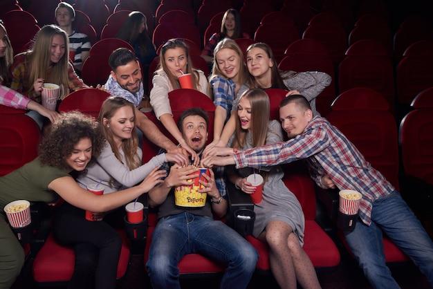 Positive und emotionale gruppe von jungen frauen und männern, die wütend sind und essen wollen, die hände zu popcorn zu einem jungen in der mitte ziehen, der schreit. mann, der großen eimer mit leckerem popcorn am kino hält.