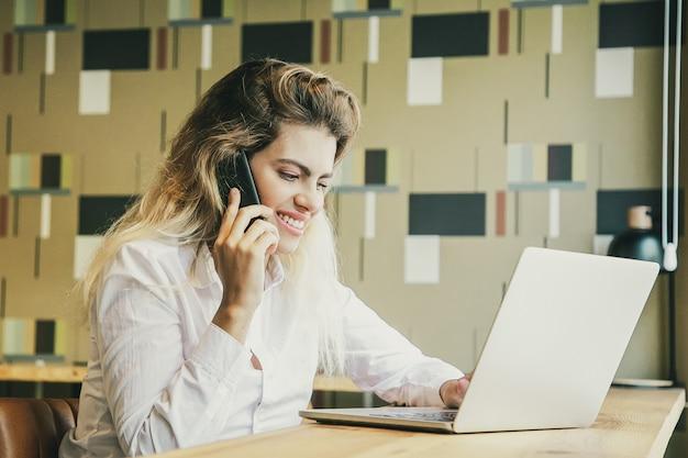 Positive unternehmerin, die am laptop arbeitet und auf handy im gemeinsamen arbeitsraum spricht.