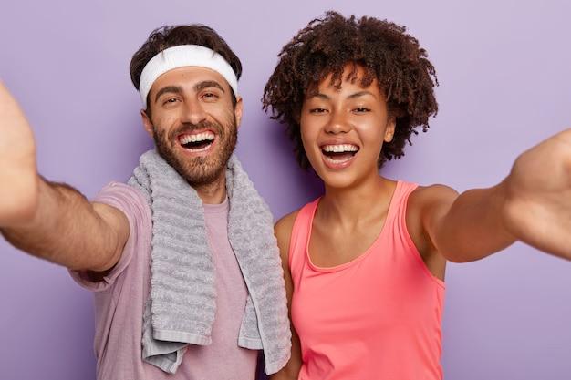 Positive vielfältige paare stehen eng und machen selfie, lächeln fröhlich, gehen gemeinsam sport, lächelnder mann trägt stirnband, handtuch am hals, sieht gesund und voller energie aus
