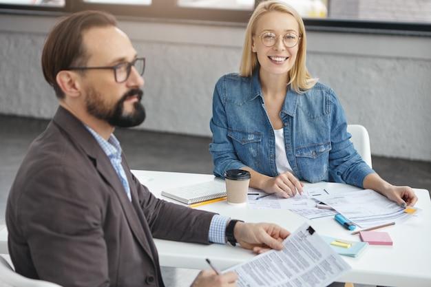 Positive weibliche assistentin und bärtiger ernsthafter männlicher unternehmer im amt