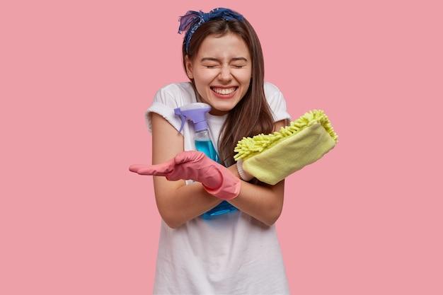 Positive weibliche grinsen gesicht, hat ein breites lächeln, weiße perfekte zähne, trägt lappen mit reinigungsmittel, ist gut gelaunt