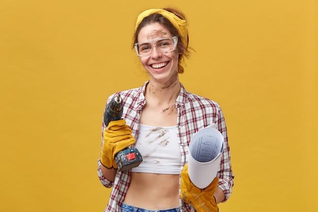 Positive weibliche wartungsarbeiterin mit schmutziger kleidung, die froh ist, ihre arbeit zu beenden, die bohrer und gerolltes papier über gelber wand isoliert hält. frau in schutzkleidung wird dinge reparieren