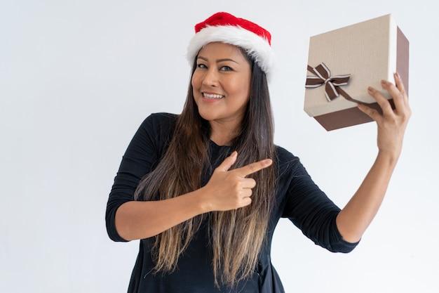 Positive weihnachtsdame, die geschenk an der kamera zeigt