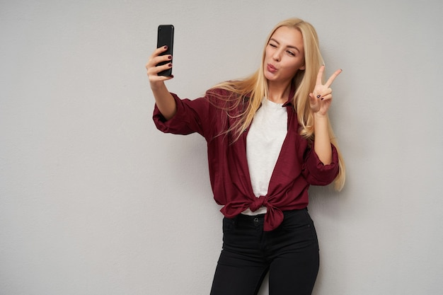 Positive ziemlich langhaarige junge blonde dame, die smartphone hält und zur kamera zwinkert, hand mit siegeszeichen erhebt, während selfie macht, über hellgrauem hintergrund posierend