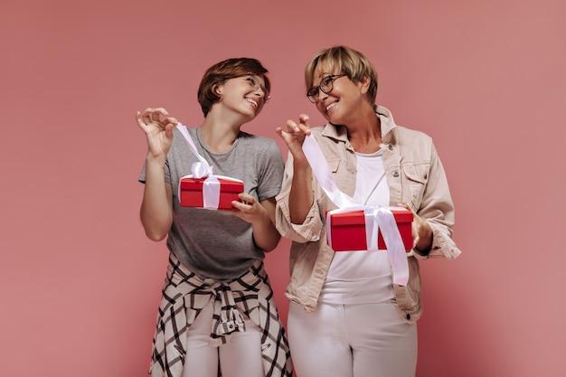 Positive zwei frauen mit kurzer moderner frisur und trendiger brille im hellen outfit, die einander schauen und bänder auf geschenkboxen auf rosa hintergrund lösen.