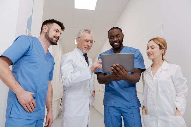 Positiven eindruck teilen. fröhliche, glückliche, qualifizierte mediziner, die im krankenhaus arbeiten und gemeinsam freizeit genießen, während sie das tablet verwenden