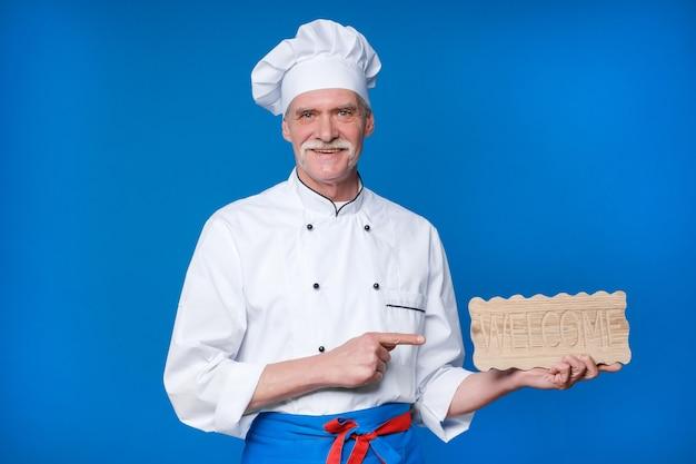 Positiver älterer koch, der holzteller mit begrüßungstext hält, in weißer uniform und mütze, die isoliert auf blauer wand posiert