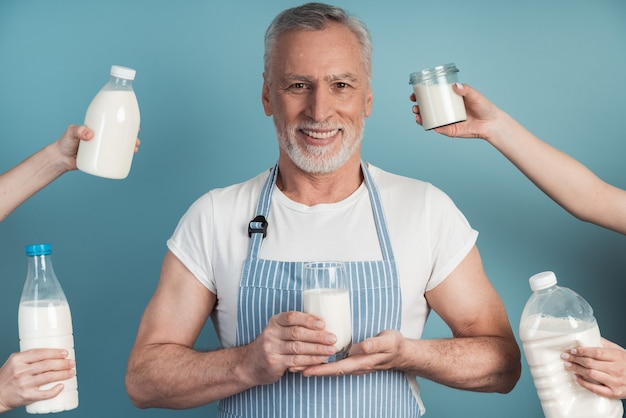 Positiver, älterer mann, der ein glas milch hält