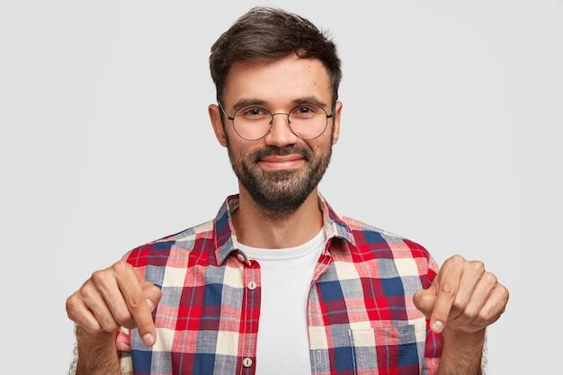 Positiver bärtiger junger mann zeigt mit fröhlich zufriedenem ausdruck nach unten, zeigt etwas auf dem boden
