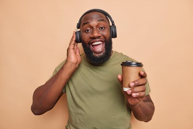 Positiver bärtiger mann hat spaß, hört musik über kopfhörer und trinkt kaffee zum mitnehmen