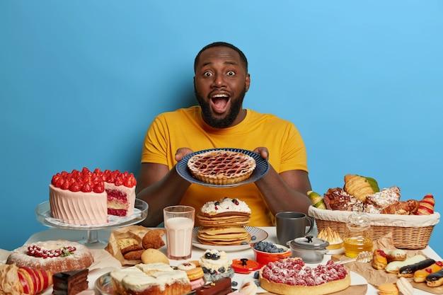 Positiver bärtiger praller mann hält teller mit hausgemachtem kuchen, isst gerne ungesunde, aber köstliche desserts, sitzt am tisch, überladen mit süßen produkten