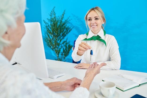 Positiver bankverkaufsleiter, der dem kunden den wohnungsschlüssel gibt
