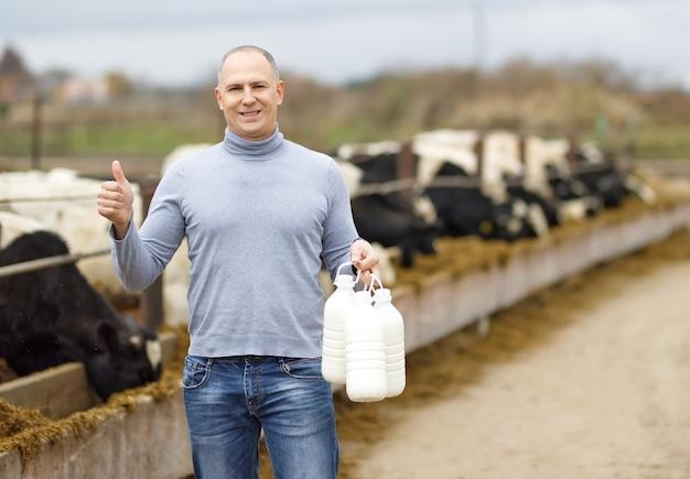 Positiver bauer mit milch der kuhfarm