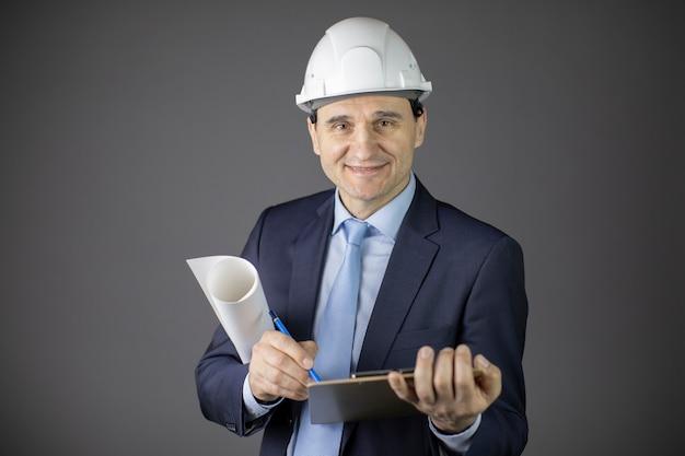 Positiver baumeister im weißen helm hält aufgerollte zeichnung und zwischenablage lächelnd