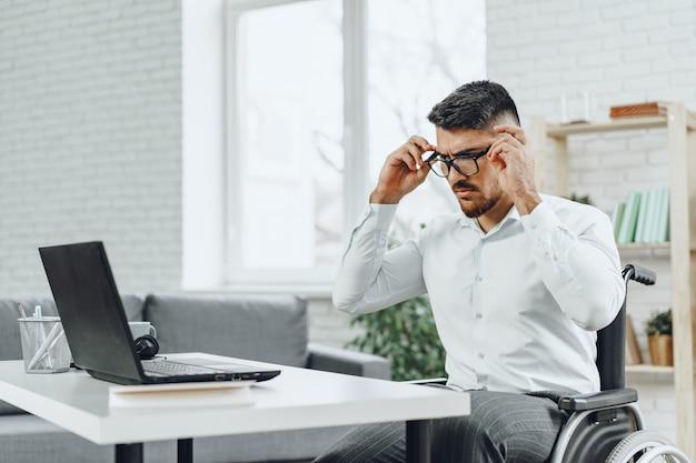 Positiver behinderter junger mann im rollstuhl, der im büro mit laptop arbeitet