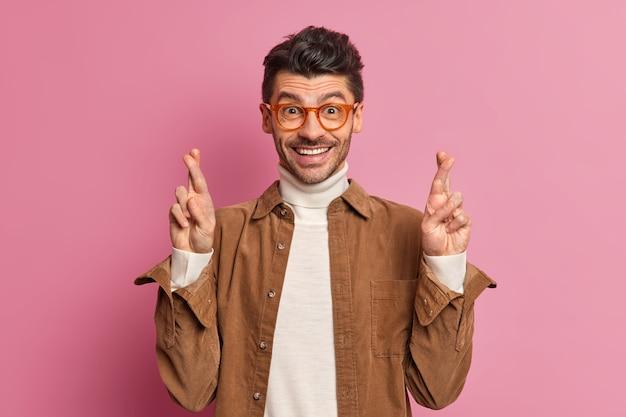 Positiver brunet-mann mit stoppeln kreuzt die finger und hofft auf viel glück