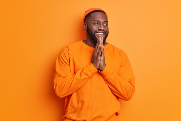 Positiver dunkelhäutiger bärtiger mann lächelt glücklich hält handflächen zusammen und glaubt an besseres