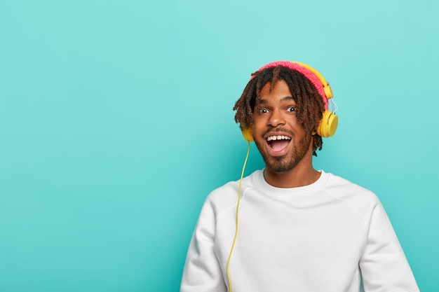 Positiver dunkelhäutiger junge hat dreadlocks, trägt eine rosa strickmütze und einen weißen pullover, modelle an der blauen wand, kopierraum für text