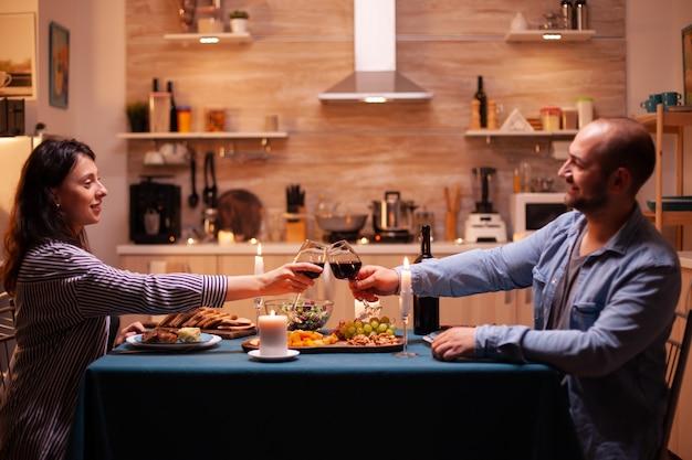 Positiver ehemann und ehefrau, die abends weingläser in der küche halten. entspannen sie sich glückliche menschen, die klirren, am tisch in der küche sitzen, das essen genießen, jubiläum im esszimmer feiern.