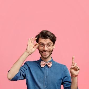 Positiver eleganter junger mann mit trendiger frisur und stoppeln, gekleidet in jeanshemd mit fliege, hat freudigen ausdruck, zeigt nach oben gegen rosa wand, hält hand am rand der brille