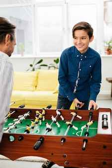 Positiver entspannter junge, der glücklich zu seinen eltern lächelt und genießt, zu hause mit ihm tischfußball zu spielen