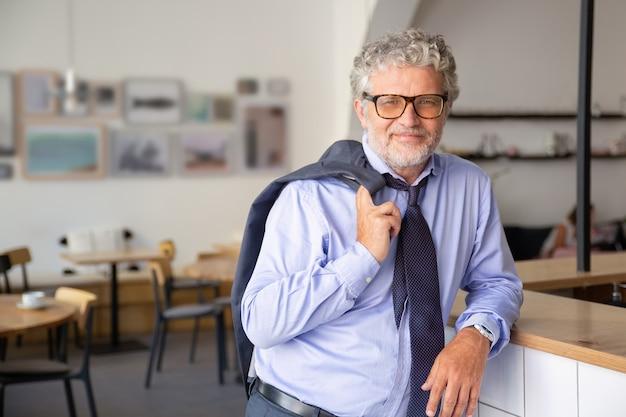 Positiver entspannter reifer geschäftsmann, der im bürocafé steht, sich auf theke stützt, jacke über schulter hält und in die kamera lächelt