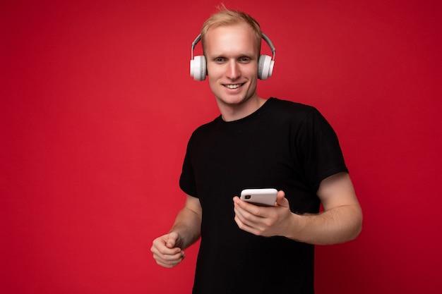 Positiver entzückender hübscher blonder junger mann mit schwarzem t-shirt und weißen kopfhörern stehend