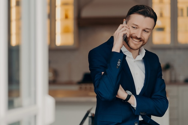 Positiver erfolgreicher geschäftsmann im anzug, der zu hause im wohnzimmer steht und mit dem partner auf dem handy spricht, smartphone hält und über job spricht. geschäftskommunikationskonzept