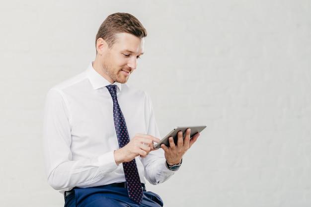 Positiver erfolgreicher männlicher geschäftsführer hält modernes touchpad, erhält benachrichtigung über netfeeds in sozialen netzwerken
