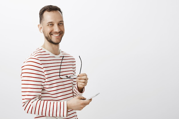 Positiver erfolgreicher männlicher geschäftsmann, der brille abnimmt, beiseite schaut und freundlich lächelt, musik auswählt, um im smartphone zu hören, kabellose kopfhörer tragend