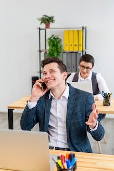 Positiver erwachsener mann, der am telefon spricht
