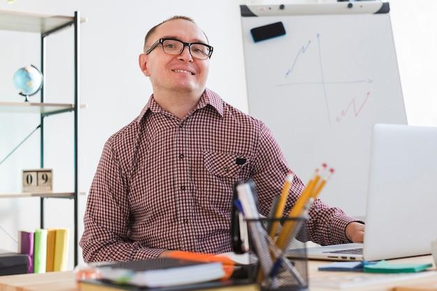 Positiver erwachsener mann im büro