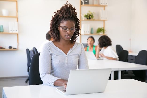 Positiver fokussierter afroamerikanerangestellter, der an computer arbeitet