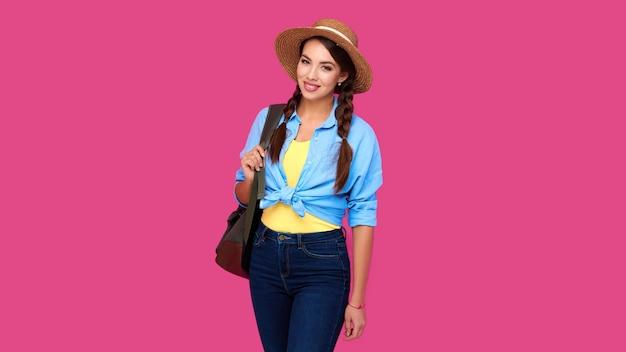 Positiver frauenreisender in der freizeitkleidung, im strohhut und im rucksack auf rosa lokalisiertem hintergrund. junger lächelnder kaukasischer tourist