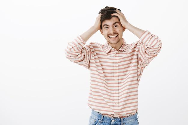 Positiver freundlicher kerl wird nie leicht verärgert. porträt des schönen glücklichen mannes mit bart und schnurrbart, händchen haltend auf dem kopf und lächelnd, während er sich an etwas erinnert, das er über graue wand vergaß