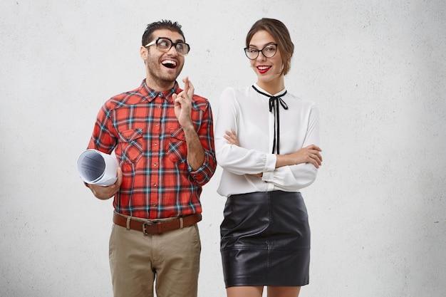 Positiver fröhlicher mann mit komischem ausdruck drückt die daumen, schaut freudig schöne frau an, die selbstbewussten ausdruck hat