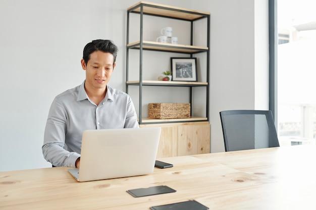 Positiver geschäftsmann, der am laptop arbeitet