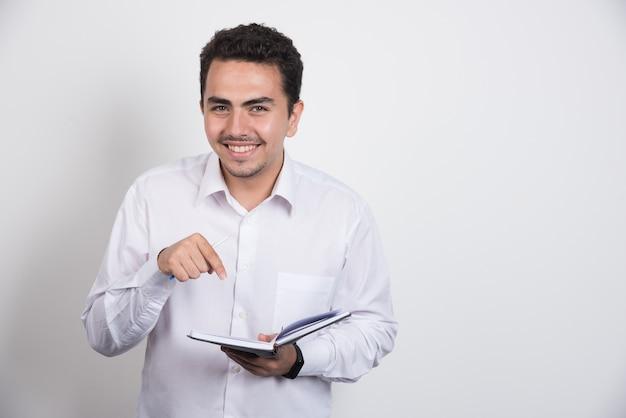 Positiver geschäftsmann, der auf notizbuch auf weißem hintergrund zeigt.