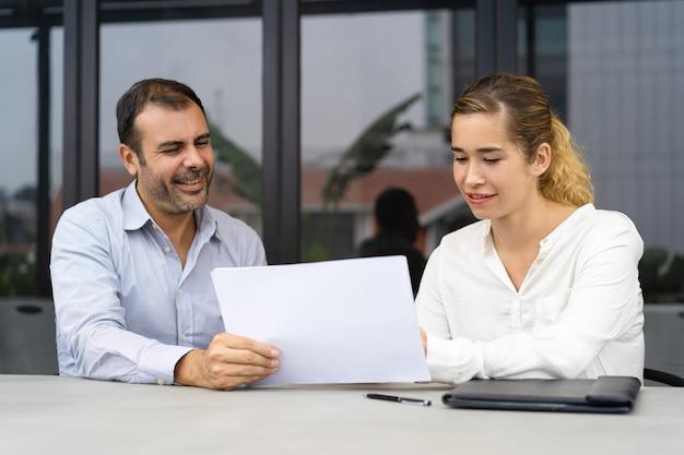 Positiver geschäftsmann, der experten bittet, dokumente zu überprüfen