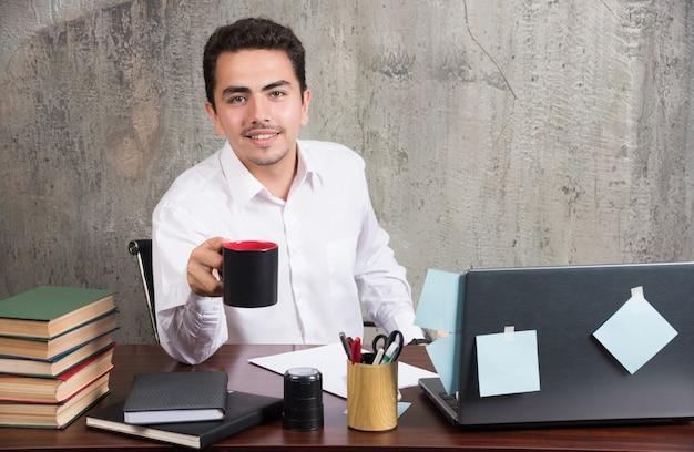 Positiver geschäftsmann, der tasse tee am schreibtisch hält.