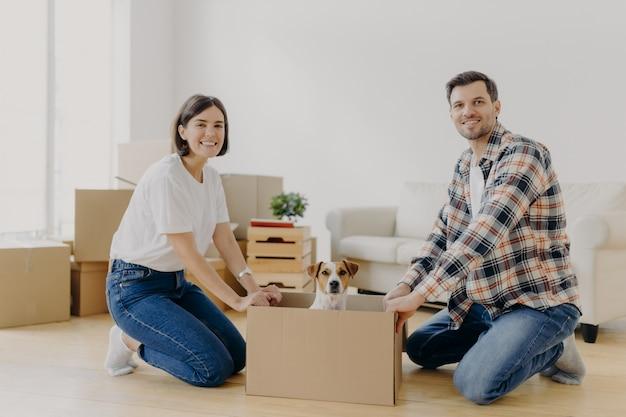 Positiver glücklicher ehemann und frau stehen auf knien nahe kartonkasten mit nettem hund
