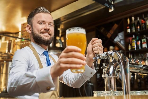 Positiver, gutaussehender barmann, der kaltes lagerbierglas hält. fröhlicher brauereiarbeiter, der an der bartheke steht und lächelt. erwachsener mann im weißen hemd und in der braunen schürze, die kamera betrachten.