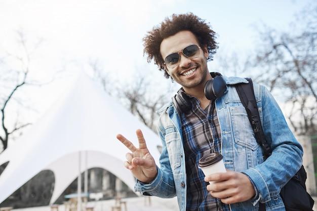 Positiver gutaussehender dunkelhäutiger mann mit afro-frisur, die frieden oder siegesgeste zeigt, während er durch die stadt spaziert, kaffee trinkt und musik hört, jeansmantel und kariertes hemd trägt