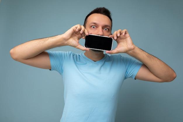 Positiver, gutaussehender junger unrasierter brunet-mann mit bart, der ein blaues t-shirt trägt, das auf blauem hintergrund isoliert ist und ein mobiltelefon mit leerem display für das modell mit blick auf die kamera hält und zeigt.