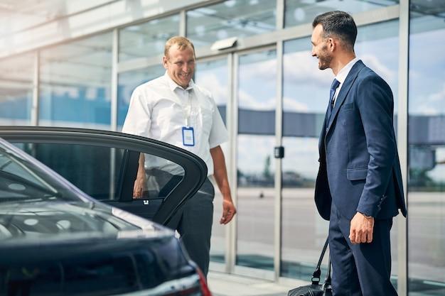 Positiver, gutaussehender reisender, der mit einem koffer zum auto geht und einen fahrer anlächelt