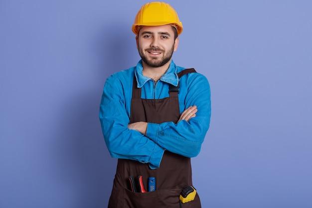 Positiver handwerker trägt gelben schutzhelm, hemd und braune schürze, bereit für die hausrenovierung.